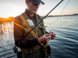 Close up candid portrait of a fly fisherman, 64 years old, tying a fly onto his line. Photographed against a setting sun on Stege Nor on the island of Møn in Denmark. Colour, horizontal format with some flare coming into the lens from the setting sun, enhancing the  mood of the picture.